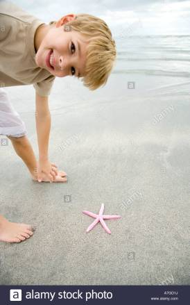 a-young-boy-with-a-starfish-A7GD1J